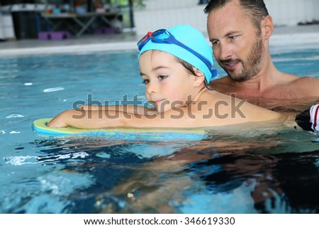 Boy child learning to swim with trainer - stock photo