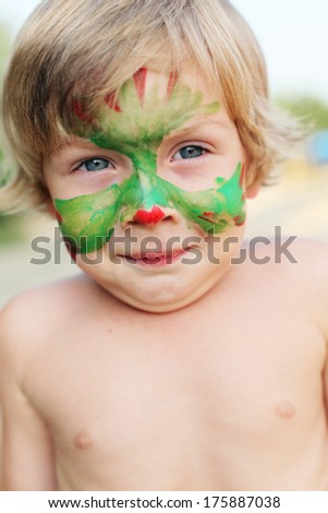 boy child with a painted mask on her face - stock photo