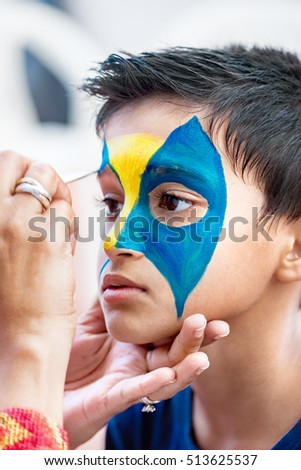 Boy child young having his face painted for fun at a birthday party
