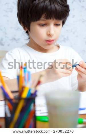boy chooses a pencil for drawing