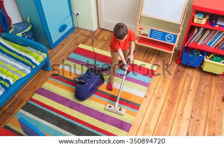 boy cleaning  floor with hoover  - stock photo