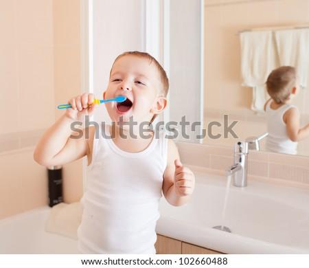 Boy cleaning teeth in bathroom - stock photo
