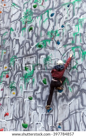 Boy climbing up a wall in an adventure park