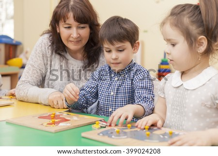 boy collects a puzzle at the table in the classroom, the teacher and the girl looking at him and smiling