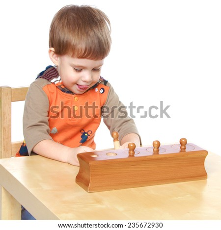 Boy collects a puzzle sitting at the table.White background, isolated photo. - stock photo