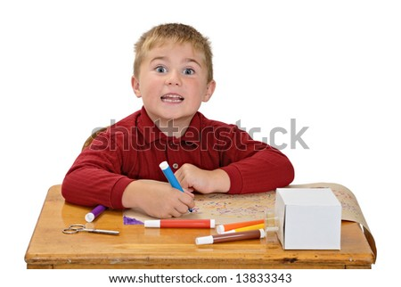 Boy coloring with silly expression - stock photo