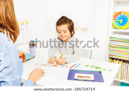 Boy colors shapes during ABA with therapist near - stock photo