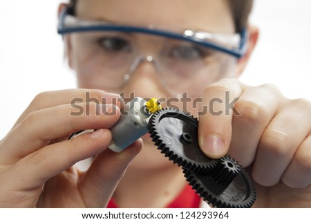 Boy connecting a motor with multiple gears while wearing safety glasses. - stock photo