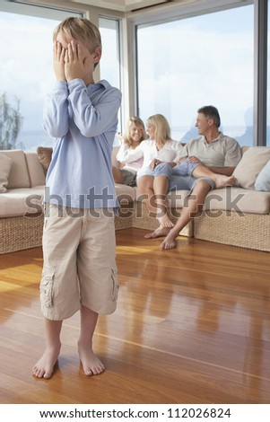 Boy covering face with hands and family in background at home