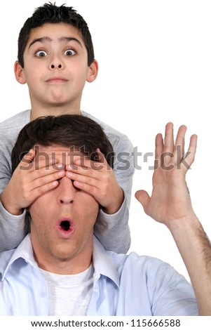 Boy covering his dad's eyes - stock photo