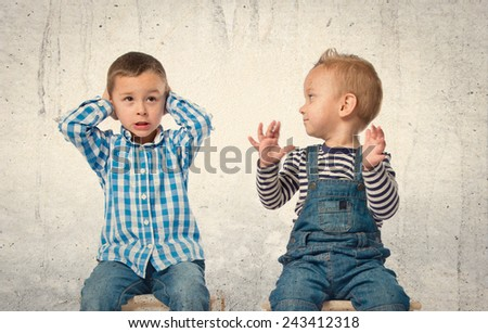 Boy covering his ears over textured background.  - stock photo
