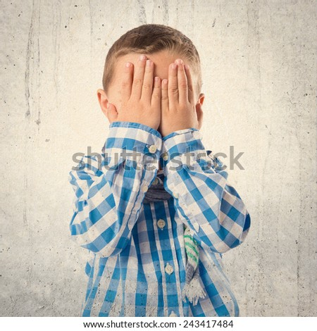 Boy covering his eyes over white background  - stock photo