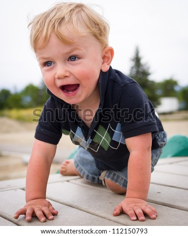 Boy crawling and laughing at playground