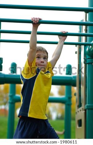 Boy Crossing Monkey Bars - stock photo