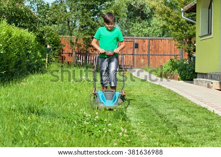 Boy cutting grass around the house in summertime - focusing on the operation - stock photo