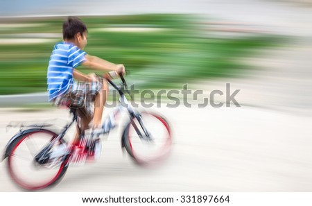 Boy cyclist in traffic on the city roadway. Intentional motion blur - stock photo