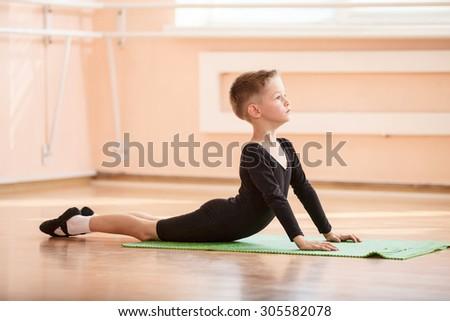 Boy dancer doing exercise at ballet dance class - stock photo