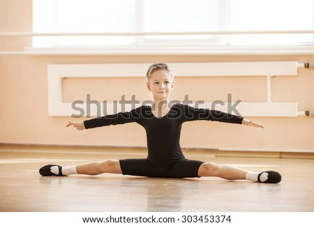 Boy dancer doing splits while warming up at ballet dance class - stock photo