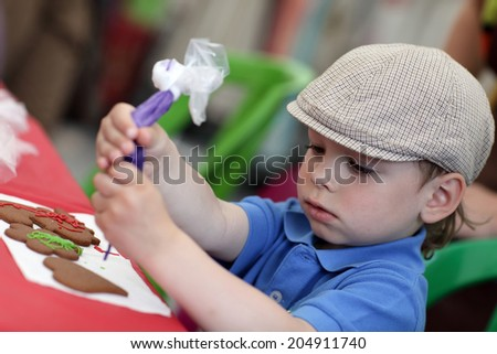 Boy decorating gingerbread shapes with a food coloring - stock photo