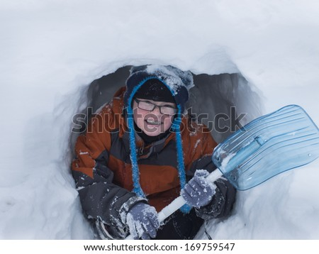 Boy digging a snow cave at the Great Teton national park.