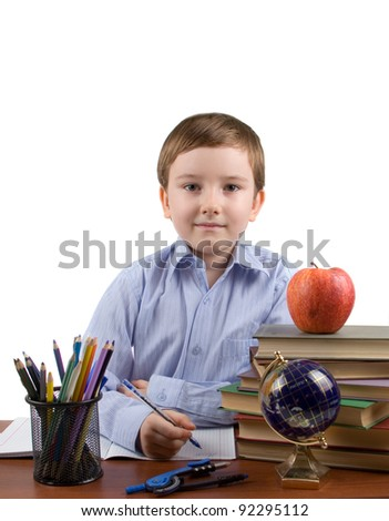Boy does homework on a table, isolated on a white background