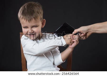 Boy does not give a  tablet , which mother want give away - stock photo