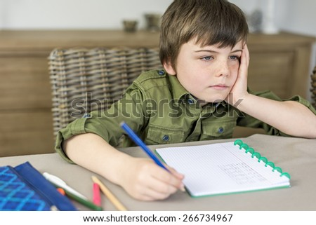 boy doesn't feel like making homework with hand under his head