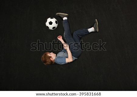 Boy doing a bicycle kick on a soccer ball - stock photo