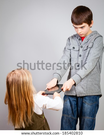 Boy dont want to share a touch pad with little sister - stock photo