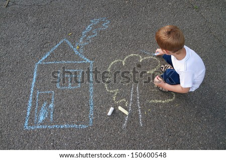 Boy drawing house and tree with chalk - stock photo