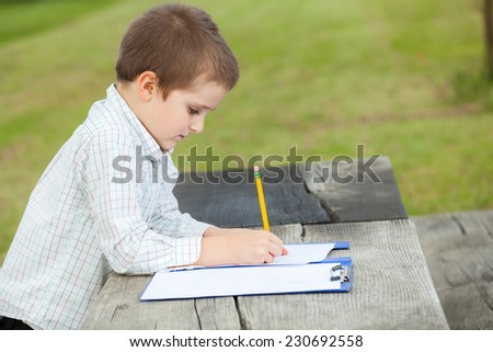 Boy drawing with a yellow pencil on a paper sitting at a wooden table in the park - stock photo