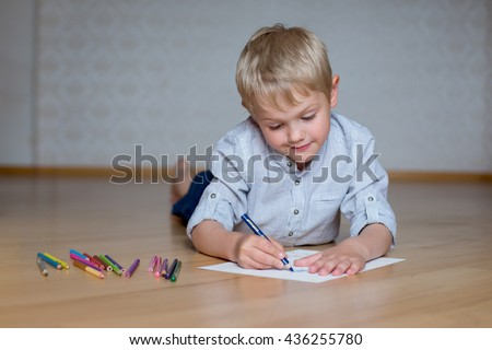 boy draws a blue pencil on a sheet of paper lying on the floor - stock photo