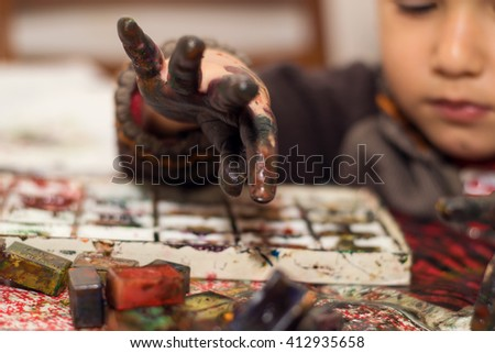 boy draws with hands soiled in a paint - stock photo
