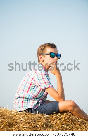 Boy dreams  on on hay stack or bale  - stock photo