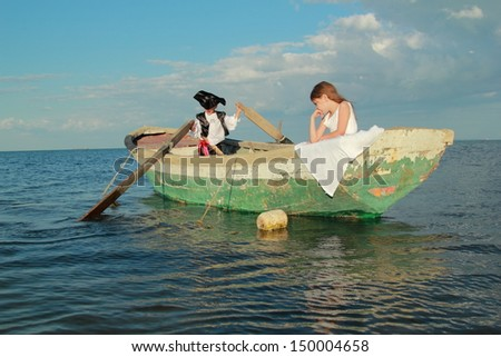 Boy dressed as a pirate and his old lady floating in a boat on a background of blue sea/Theatrical performance of the pirates outdoors - stock photo