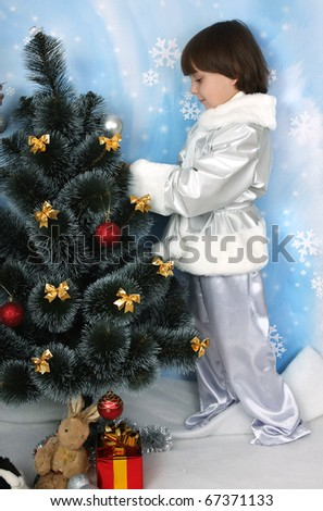 boy  dressed as a silver dress decorate a Christmas tree