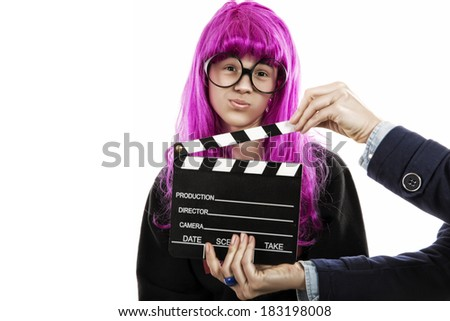 boy dressed as a woman with large glasses and pink wig. Woman hands holding a slate of films. humorous photo - stock photo