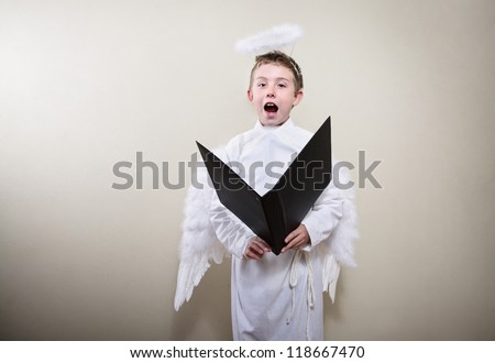 Boy dressed as an angel singing - stock photo