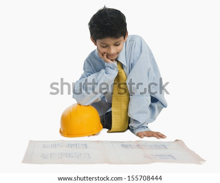 Boy dressed as an architect and working on a blueprint - stock photo