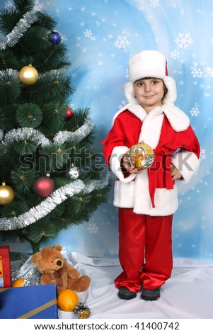 boy dressed as Santa Claus holding the ball near the Christmas tree