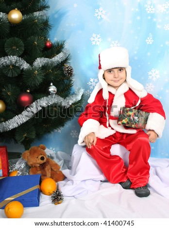 boy dressed as Santa Claus with a gift under the tree