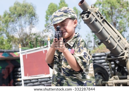 boy dressed like a soldier with a gun in barracks