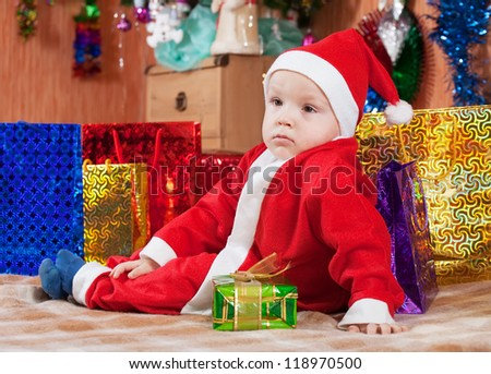 Boy dressed like Santa Claus with  Christmas gifts at home - stock photo