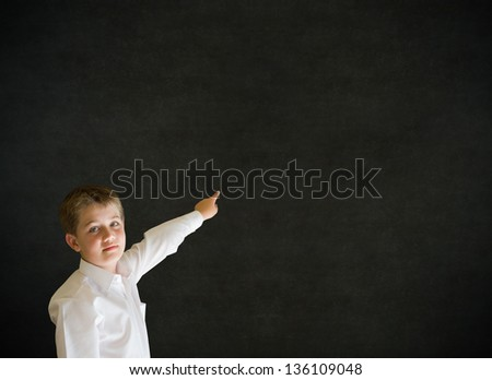 Boy dressed up as business man, teacher or school student pointing on blackboard background - stock photo