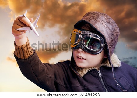 Boy dressed up in pilot outfit at sunset sky