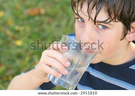 boy drinking a glass of water - stock photo