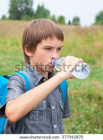 Boy drinking still water from pet bottle outdoors - stock photo