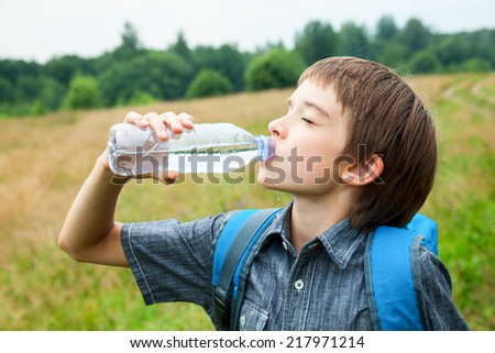 Boy drinking water from pet bottle outdoors - stock photo