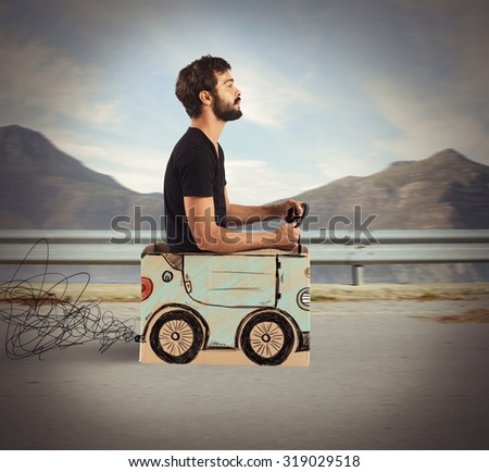 Boy driving cardboard car in mountain road - stock photo