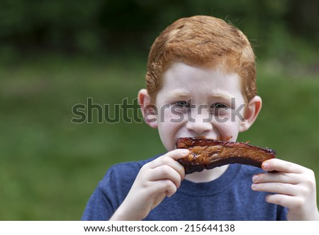 Boy eating a BBQ rib outside getting messy
